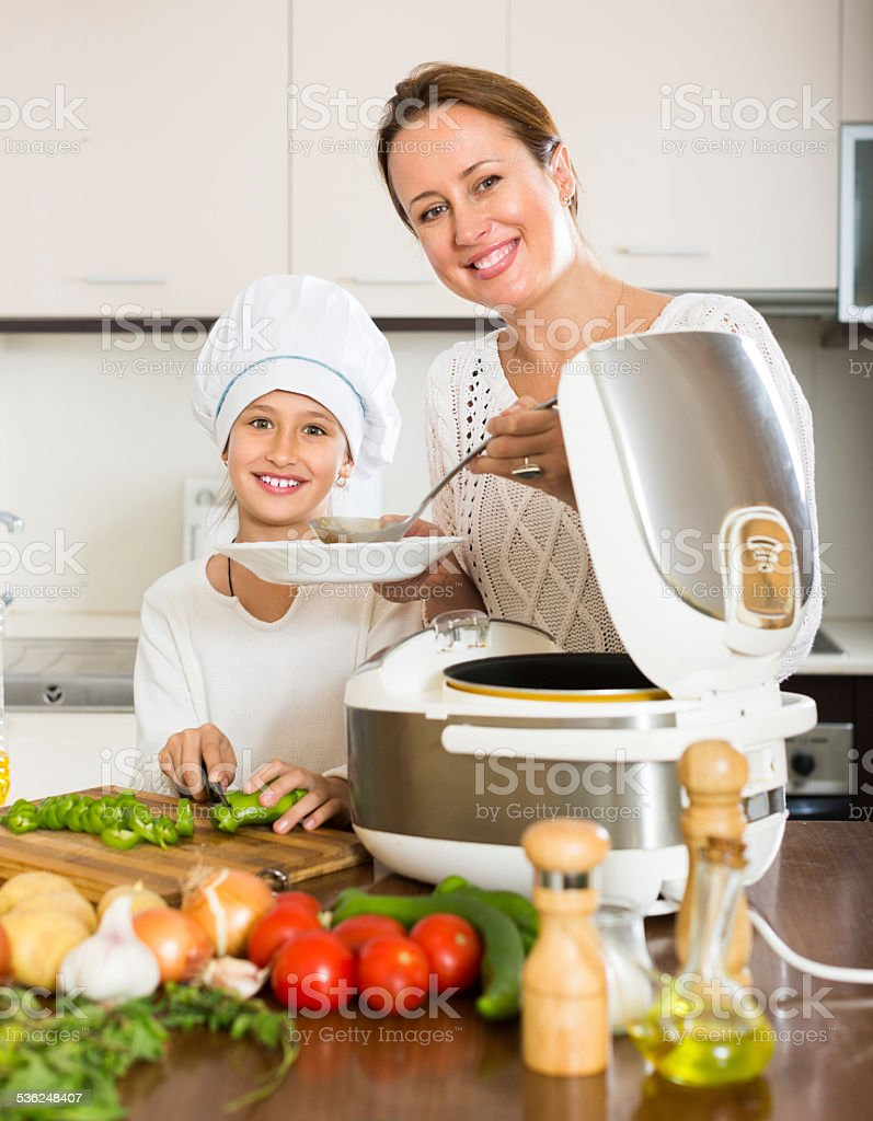 Girl and her mom with rice cooker stock photo