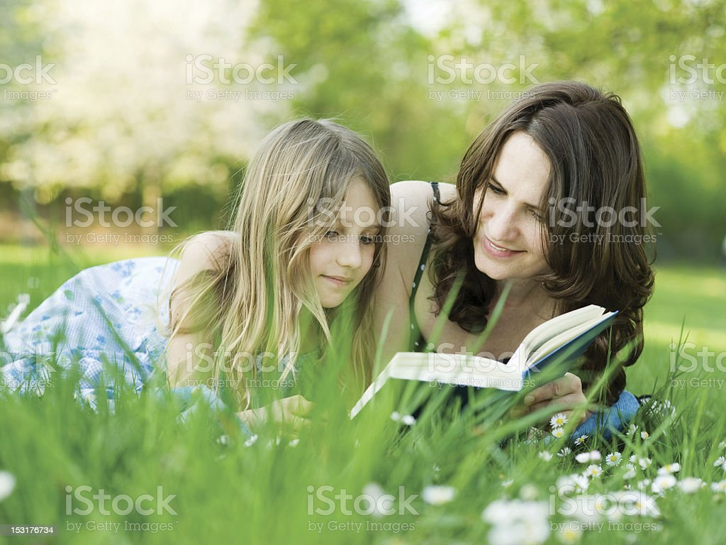 Girl and her mommy read a book amid green grass royalty-free stock photo