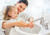 istock girl and her mother are washing hands 1037250058