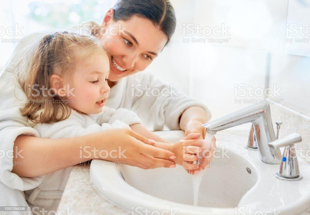 Mädchen und ihre Mutter sind Hände waschen. – Foto