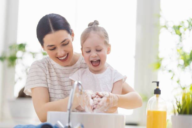 girl and her mother are washing hands stock photo