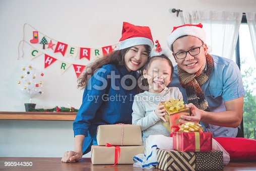 istock girl and her parents open christmas gift boxes at home 995944350