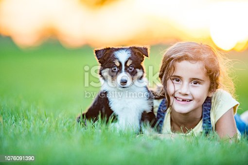 A girl is lying down on her front in a grassy field. Her puppy is sitting beside her. It is summertime.