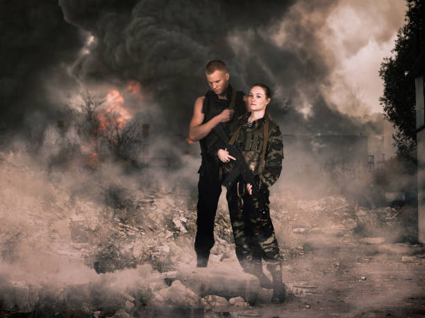 girl and man in military camouflage uniforms among the ruins stock photo