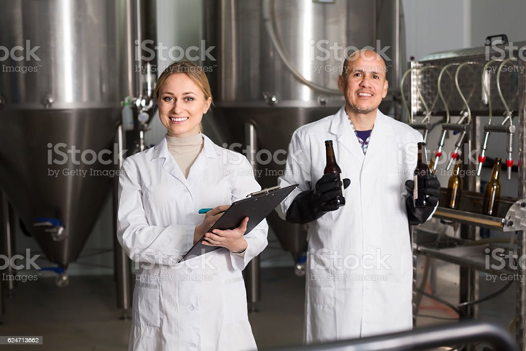 Girl and man in modern beer production facility stock photo