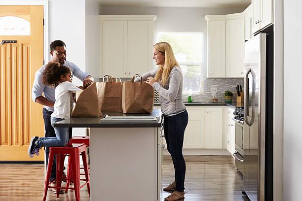 mädchen und gemischtes eltern einkaufstaschen in der küche auspacken - küche aus paletten stock-fotos und bilder