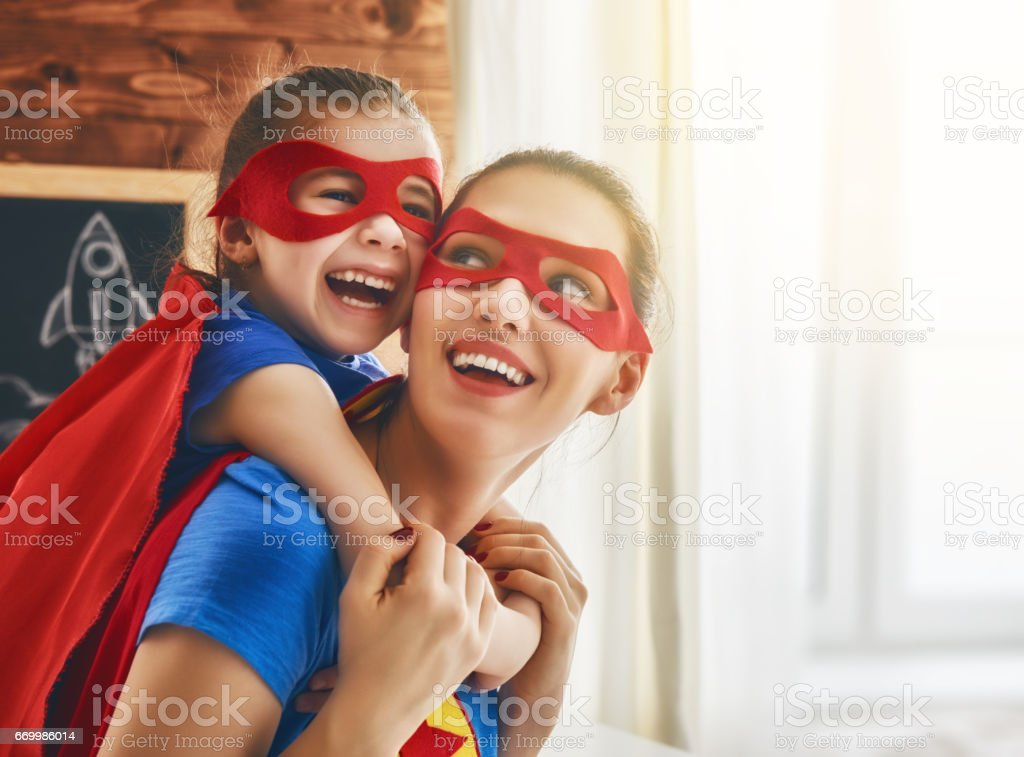 Girl and mom in Superhero costume stock photo