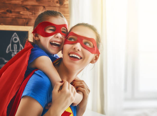 Girl and mom in Superhero costume stock photo