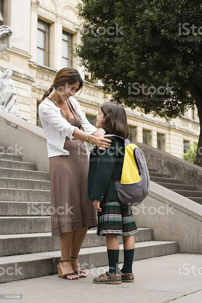 Girl and mother outside school stock photo