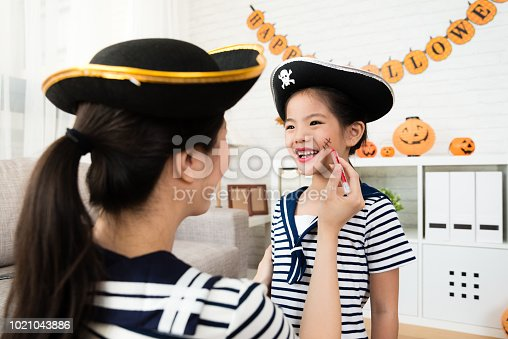 pirate girl and mother play Halloween makeup game and sketch scars on the face at home