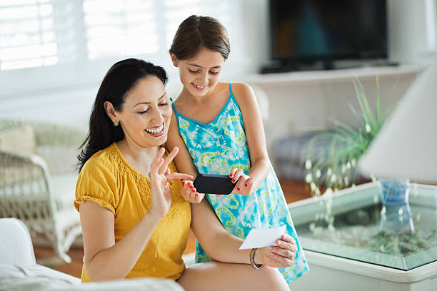 girl and mother using smart phone to deposit check - deposit slip stock photos and pictures