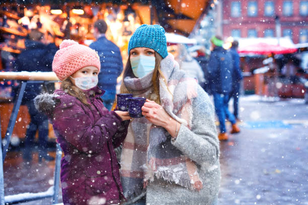 Girl and mother with cup of steaming hot chocolate. Child woman on Christmas market in Germany. People with masks as protection against corona virus. Covid pandemic time in Europe and in the world. stock photo