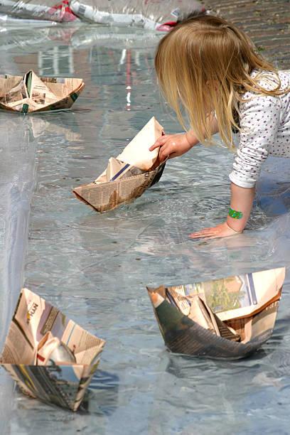 mädchen und paperboats - basteln mit zeitungspapier stock-fotos und bilder
