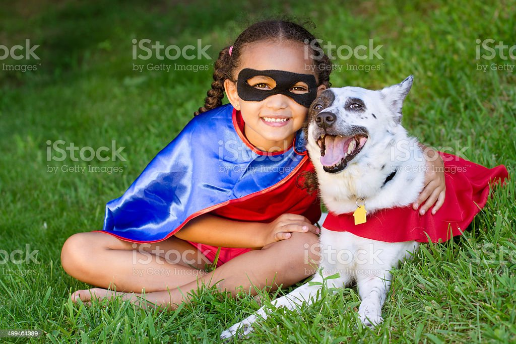 Girl and pet dressed up as super heroes stock photo