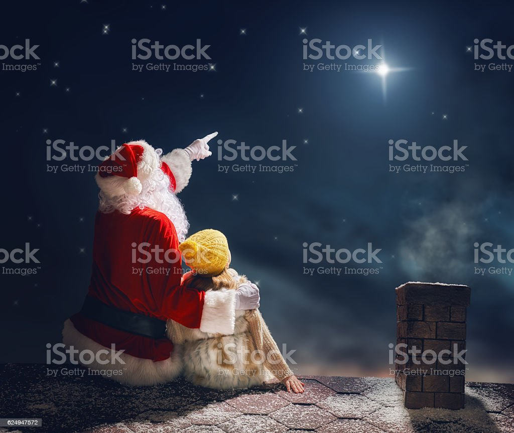 girl and Santa Claus sitting on the roof stock photo
