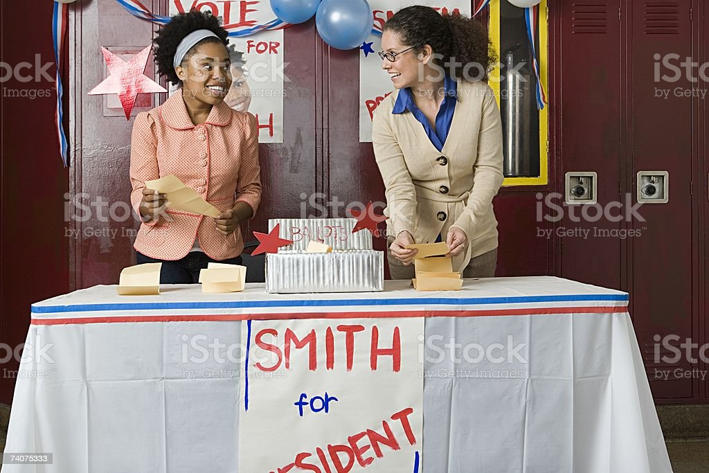 Girl and teacher counting votes stock photo