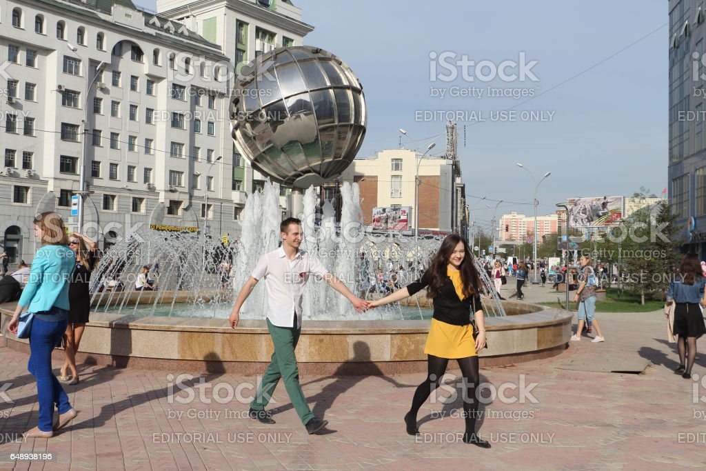 NOVOSIBIRSK, RUSSIA - MAY,9: Girl and the guy go down the street, having joined hands, at the fountain in the form of the globe. Taken on MAY 9, 2015 in Novosibirsk, Russia. stock photo