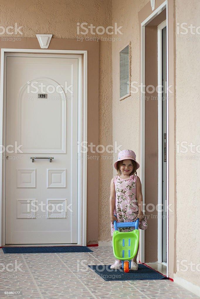 Girl and toy wheelbarrow royalty-free stock photo