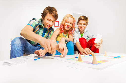 istock Girl and two boys playing table game at home 537701409