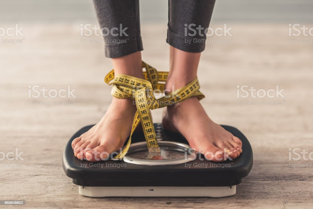 Girl and weight loss Cropped image of woman feet standing on weigh scales, on gray background. Legs winded with a tape measure Adult Stock Photo