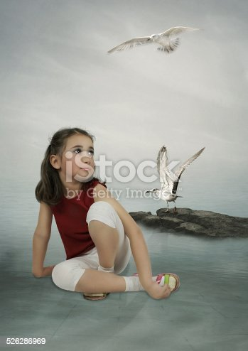 Little girl is sitting near the water and looking at the white gulls
