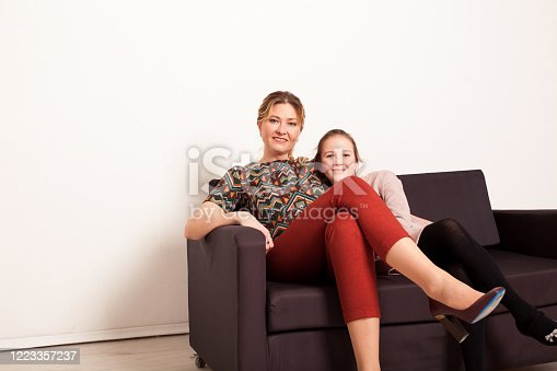 1003539592 istock photo girl and woman lies on a black sofa in homeclothes with pillows 1223357237