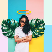 girl angel with wings made of palm leaves and a halo over her head in a white dress on a colored background