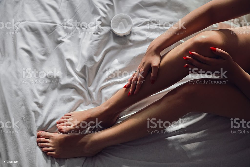 Girl applaying cosmetic on her legs stock photo