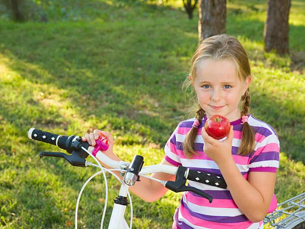 Girl, apple, bike and park stock photo
