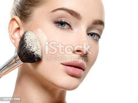 istock Girl applies  powder  on the face using makeup brush. 1037624998