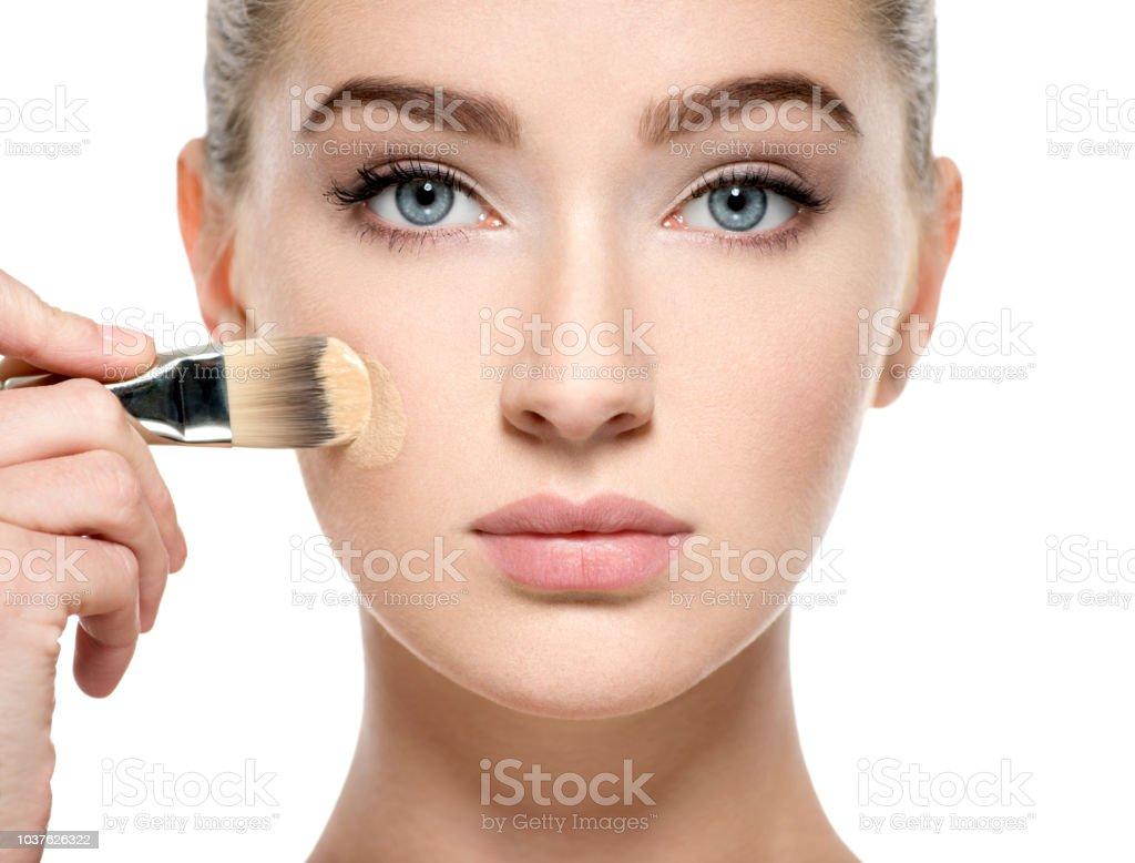 Girl applies  tonal foundation on face use makeup brush stock photo