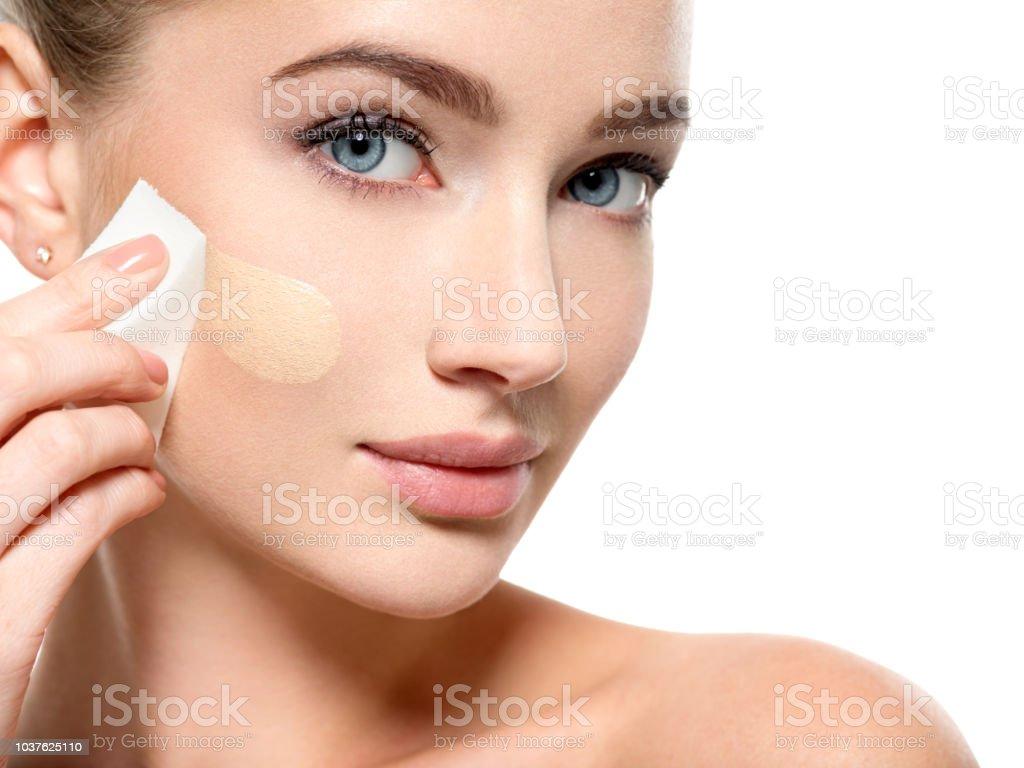 Girl applies  tonal foundation  on the face use sponge stock photo