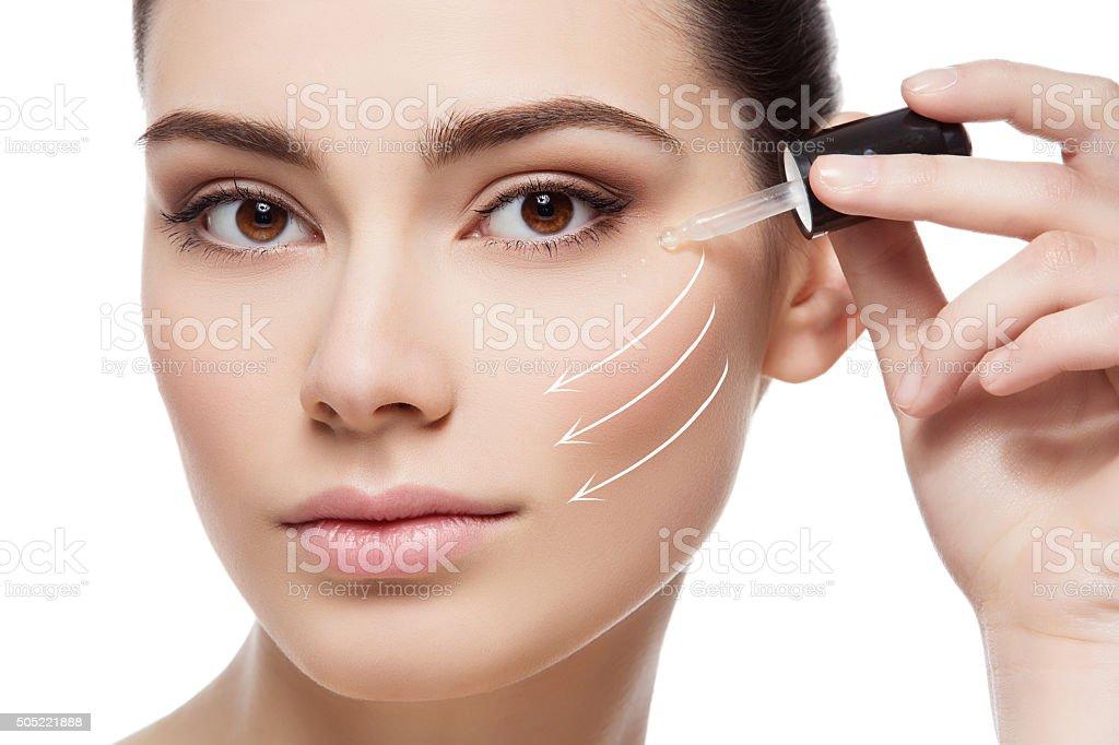 Girl applying anti wrinkle serum stock photo