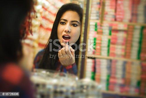 istock Girl applying lipstick, checking in mirror at cosmetics shop. 618728006