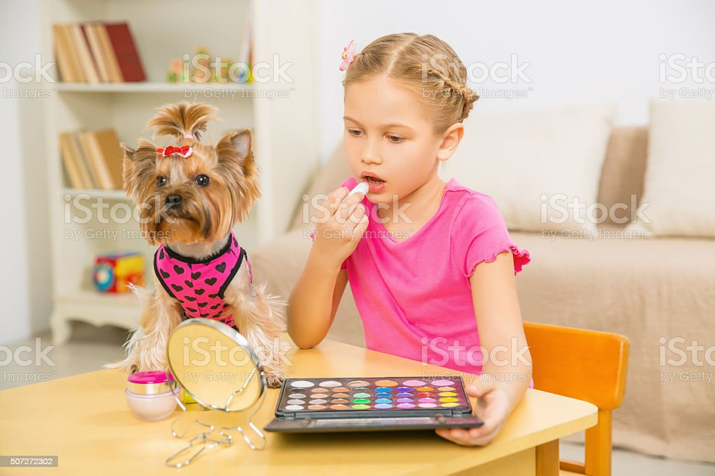 Girl applying make up and terrier beside her stock photo