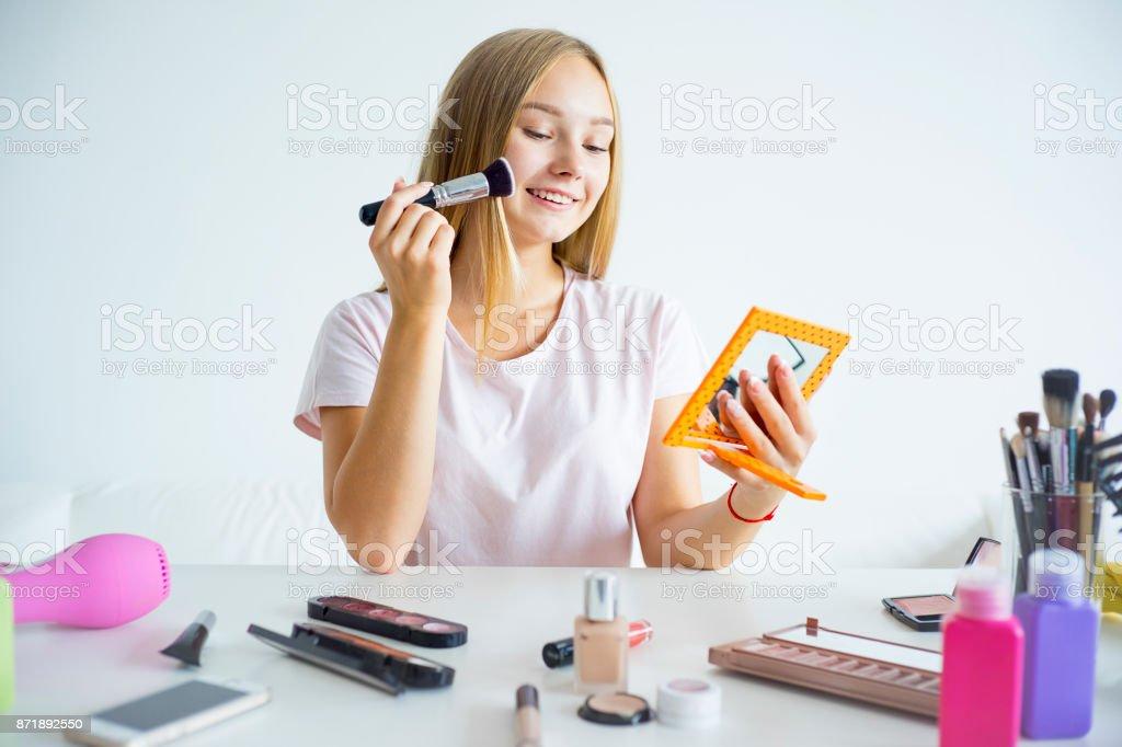 Menina aplicando maquiagem - foto de acervo