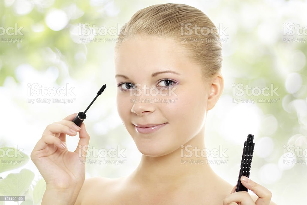 girl applying mascara on a green background royalty-free stock photo