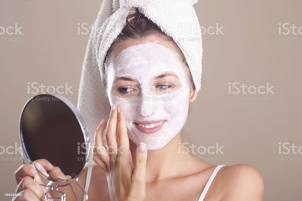 girl applying  mask on  face and looking in the mirror stock photo