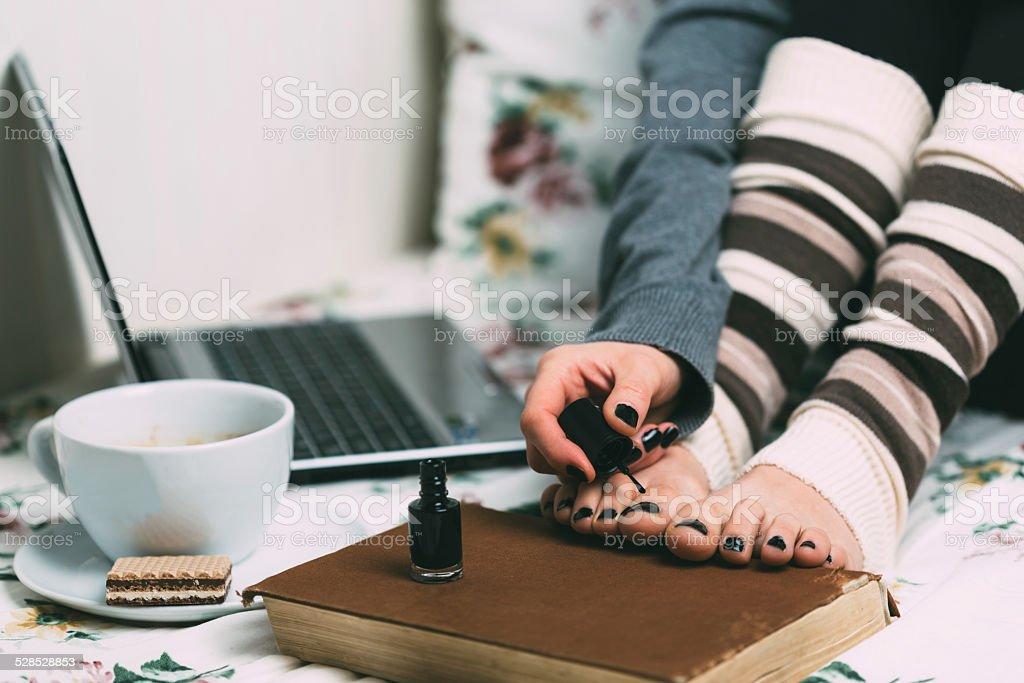Girl applying nailpolish at toenails stock photo