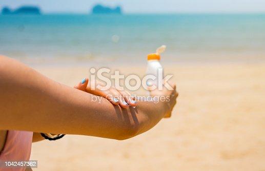 istock Girl applying sun lotion on the beach 1042457362