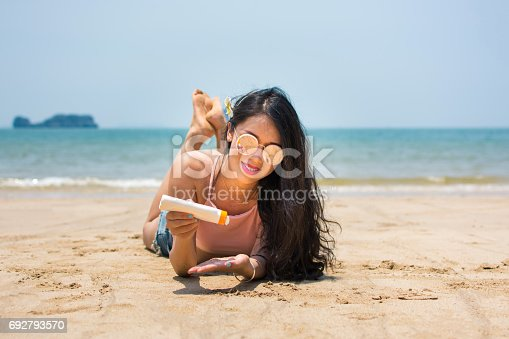 istock Girl applying sun lotion on the beach 692793570