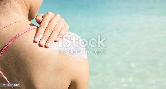 istock Girl applying sun lotion on the beach 821498132