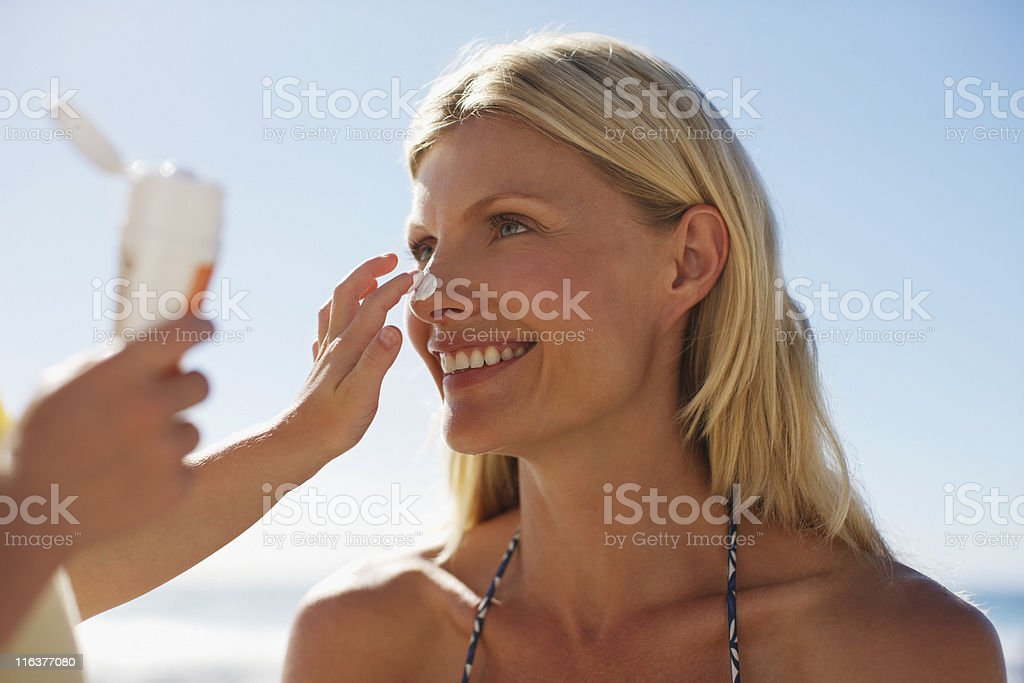 Girl applying sunscreen to mothers nose stock photo