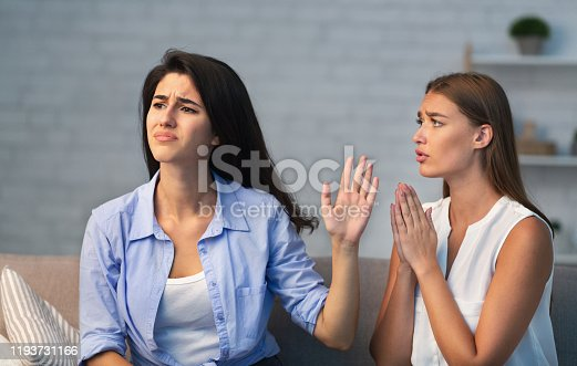 Miserable Girl Asking Indifferent Friend For A Favor Begging Holding Hands In Prayer Gesture Sitting On Sofa Indoor. Selective Focus