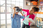 Girl holding digital tablet while assisting boy to wear VR headset. School children using technologies in classroom. They are in elementary school.