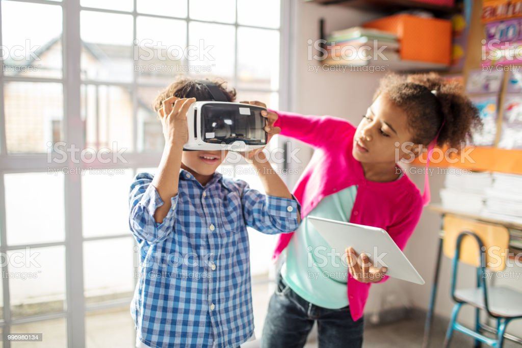 Girl assisting boy to wear VR headset in class stock photo