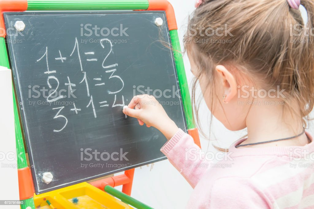 girl at a board solves examples on mathematics. Training of the child. stock photo