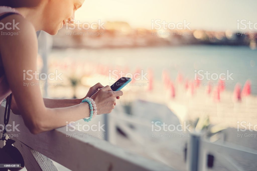 Girl at a veranda text messaging on the phone stock photo