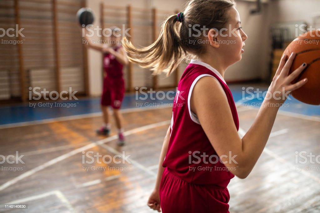 Teenage girl playing basketball game at school gym during training...