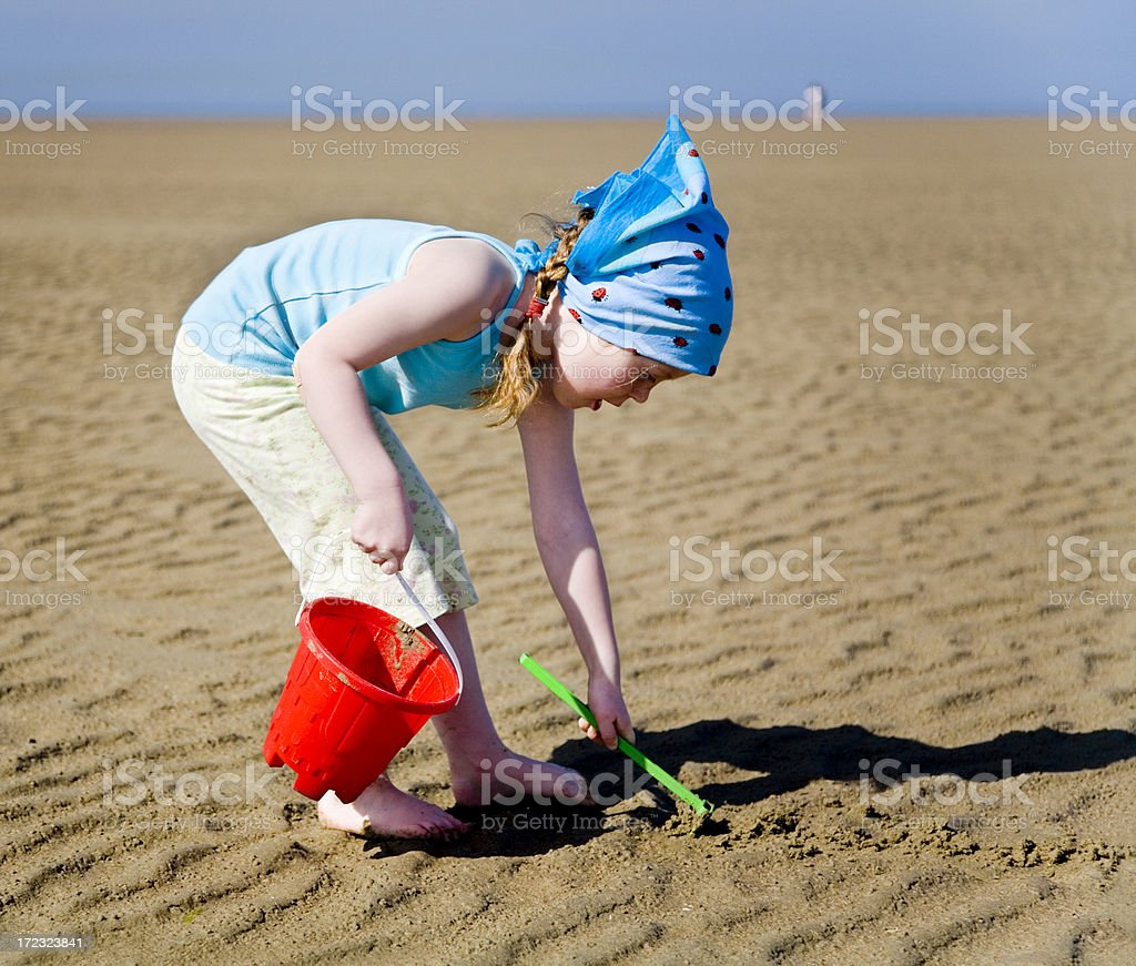 girl at beach with bucket and rake Little 4 year old girl at the beach. Beach Stock Photo